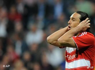 Disappointed Munich soccer striker Luca Toni holds his hands over his head