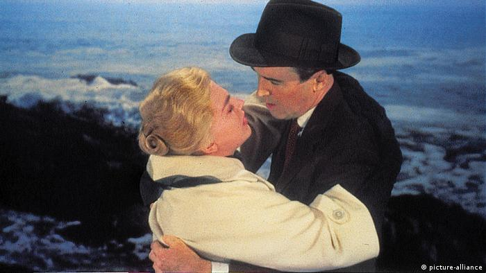 Man in a black suit with a hat and blonde woman in a light jacket hug on the seaside