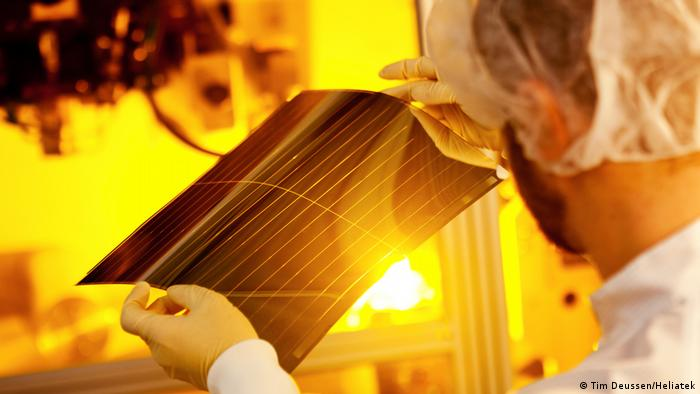 Worker holding up lightweight film for solar energy production against the sun