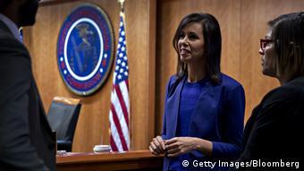 Eine Frau in blauen Blazer unterhält sich mit zwei Personen (Foto: Getty Images)