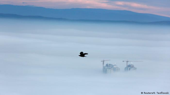 Buildings are seen as fog blankets the city of Skopje