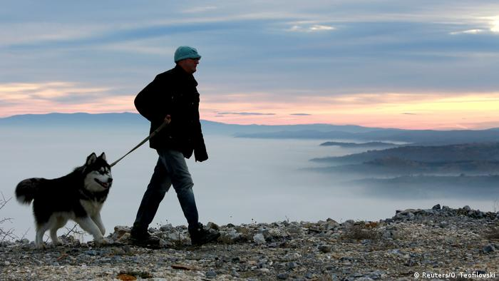 A man walks his dog as fog blankets Skopje