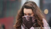 A woman covers her face during a period of fog and air pollution in Skopje, Macedonia December 15, 2017. REUTERS/Ognen Teofilovski