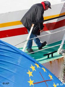 A fisherman on his boat, onto which he attached a crossed flag of the European Union