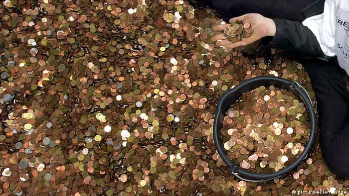 A hand holds out a bunch of pennies above a floor covered in them (picture-alliance/dpa)