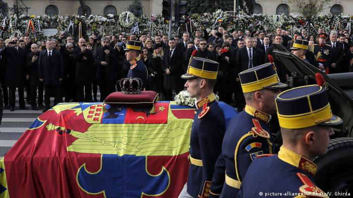 Honor guard escort a flag covered coffin of King Michael throguh Bucharest.