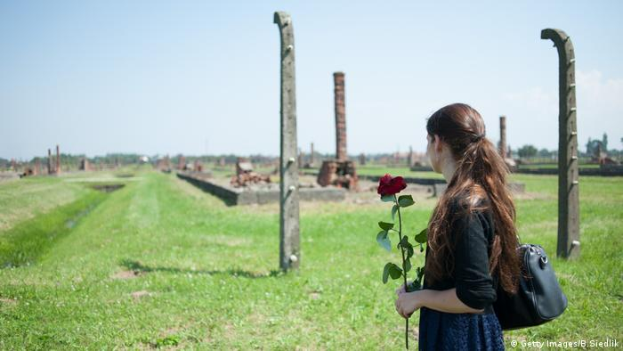 A woman holds a flower on August 2, 2014 during the commemoration of the 70th anniversary of the the Roma Genocide in Auschwitz II-Birkenau, former Nazi concentration camp in Oswiecim