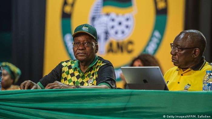 Former South African President Jacob Zuma stares out at the crowd on a podium at the ANC party conference. Current President Cyril Ramaphosa sits next to him with a laptop.