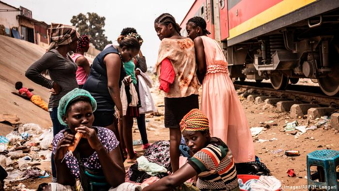 A group of women pick though clothes for sale on a dirt track along a railway line in Luanda