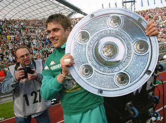 SV Werder Bremen's Croatian player and scorer of the first goal Ivan Klasnic runs with a cardboard cutout replica of the German Soccer champion trophy after his team's 3-1 victory over FC Bayern Munich in their German first division soccer match in Munich, Germany, Saturday, May 8, 2004. (AP Photo/Diether Endlicher)