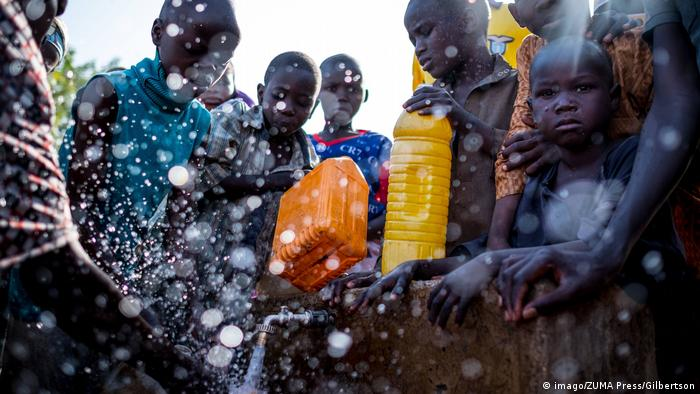 Children fight to fill up water bottles at a water point