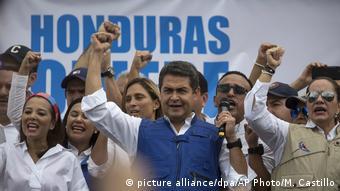 Honduran President Juan Orlando Hernandez raises his right fist as he speaks to supporters