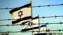 NEVE DEKALIM, -: Israeli flags flutter in the wind behind a barbed wire fence during a ceremony to mark the end of military presence in the Gaza Strip at an evacuated army base near the former southern Gaza Strip settlement of Neve Dekalim, 11 September 2005. The Israeli army lowered its flag over the dust of the Gaza Strip today as the sun set on the last day of Israel's military presence in the Palestinian territory. AFP PHOTO/DAVID FURST (Photo credit should read DAVID FURST/AFP/Getty Images)