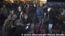 Passagiere warten im unbeleuchteten Flughafengebäude darauf, dass es weitergeht