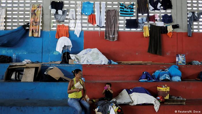 Venezuelan woman and her child sit at a gym which has turned into a shelter for Venezuelans