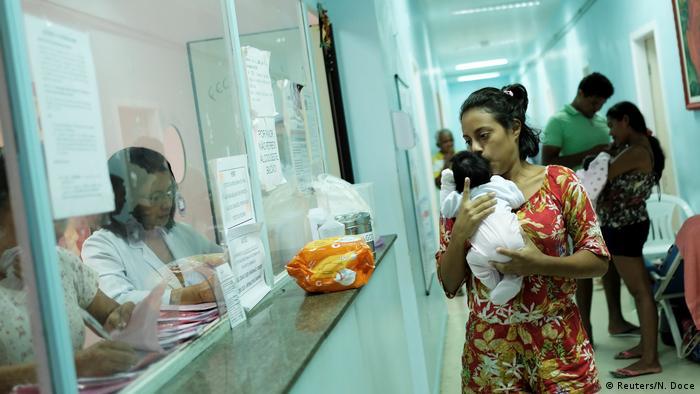 Mulher com bebê no colo em corredor de hospital