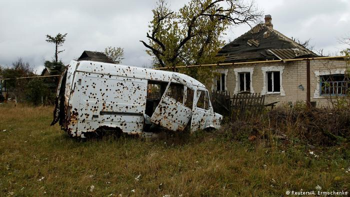 Изрешеченный шрапнелью автофургон и полуразрушенный дом в Донецкой области