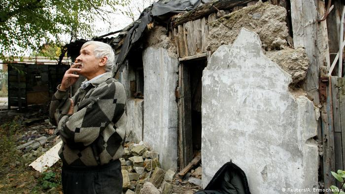 Мучжина курит возле его разбитого дома