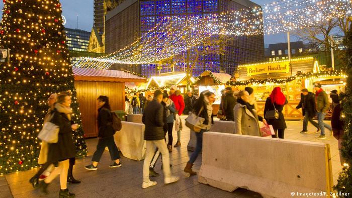 Menschen gehen bei abendlicher Lichterstimmung durch Sperren mit Betonklötzen auf den Weihnachtsmarkt (Foto: Imago)