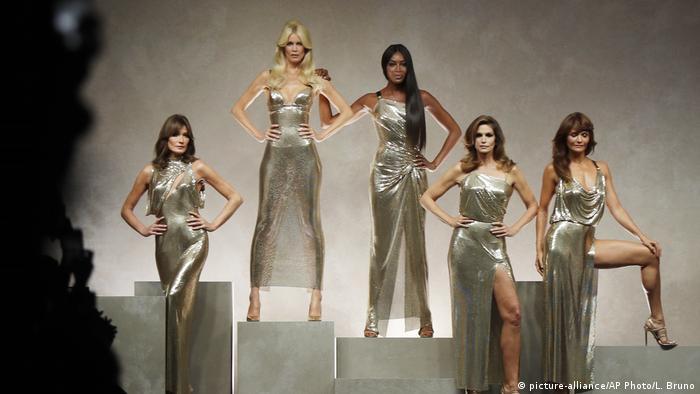 Vier Frauen oder Modemodels posieren in silbrig-goldenden Kleidern auf Podesten auf einer Bühne Foto: Luca Bruno/AP
