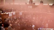 Members of Albania's parliament are seen through a haze of smoke inside the chamber.