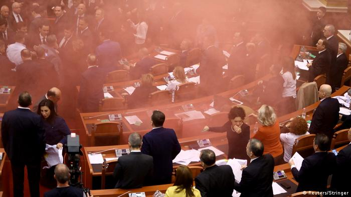 Smoke wafts through the packed Albanian parliament