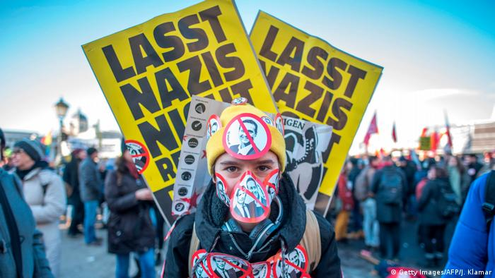 A protester against the new government in Austria is covered in anti-Nazi stickers