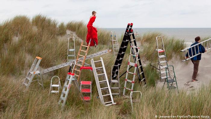 Ladders in the sand dunes, one carried by a man, with a woman in a red dress in the background (Leeuwarden-Fryslân/Tryntsje Nauta)
