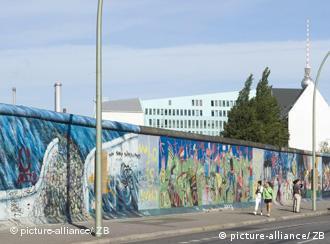 Passanten laufen an einen Rest der Mauer in Berlin entlang (Foto: dpa)
