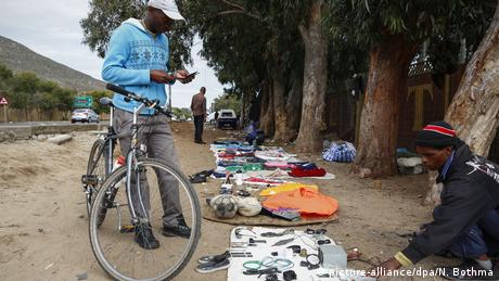 A man with a bicycle stops by an informal trader (picture-alliance/dpa/N. Bothma)