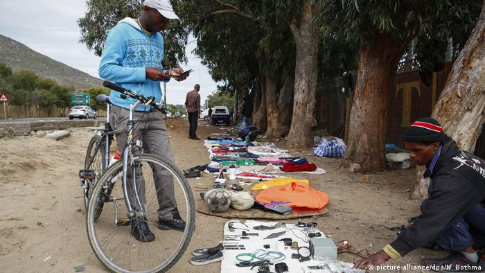A man with a bicycle stops by an informal trader