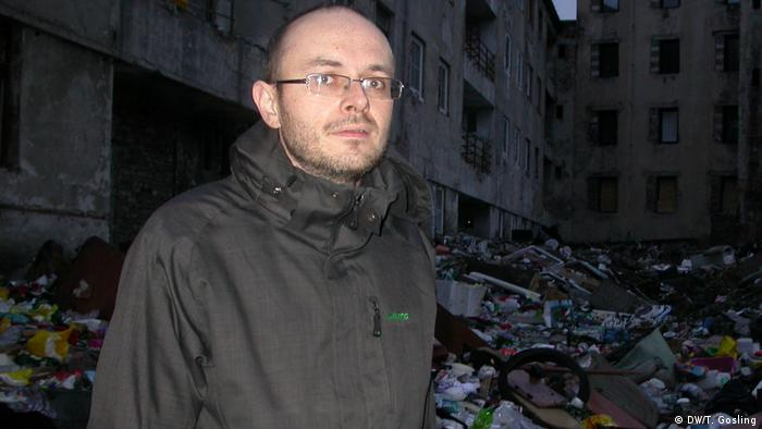 Miroslav Broz of the NGO Konexe stands in front of garbage piled high in the courtyrad of a run-down building in Predlice, Usti nad Labem