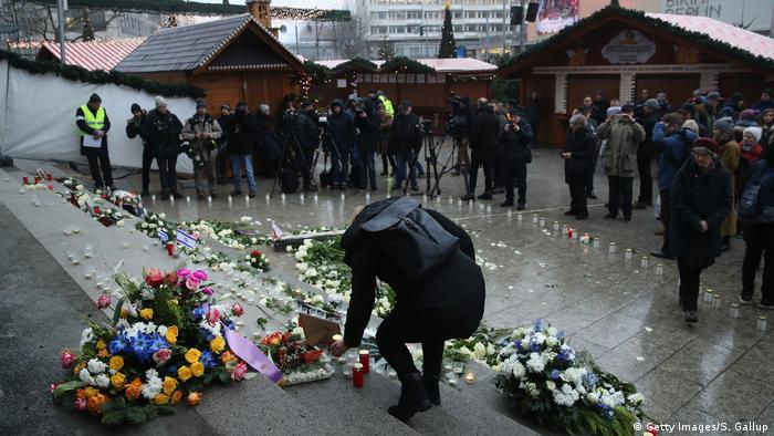 A person places a candle in front flowers at a memorial at the Breitscheidplatz Christmas market