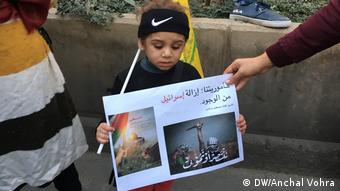 A mother hands protest material to her toddler at a Beirut pro-Hezbollah rally following Trump's Jerusalem announcement