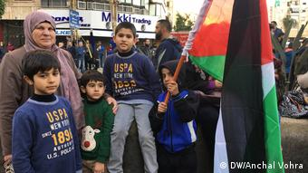 A mother and children waving a Palestinian flag at a Hezbollah rally in Beirut