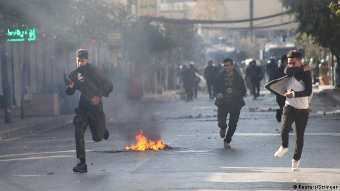 Kurdish protesters running through the streets of Sulaimaniyah