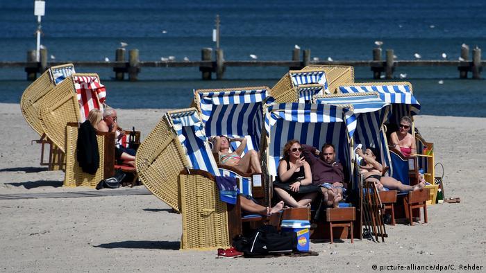 Отдыхающие загорают в пляжных корзинах
