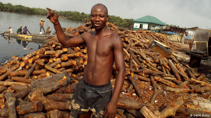Domingo Philip stands on top of a pile of logs next to the Niger River