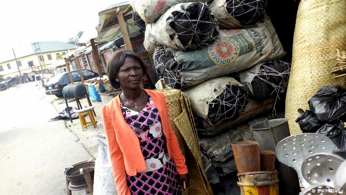 A woman stands next to piled up sacks of charcoal