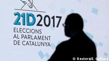A man stands in front of a sign in the main press center for tomorrow's regional elections in Barcelona, Spain December 20, 2017. REUTERS/Eric Gaillard