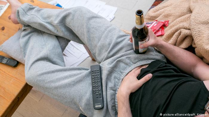 Čovjek sjedi s pivom u ruci