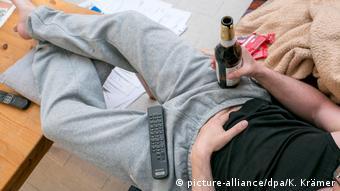 Мужчина сидит на диване с бутылкой пива в руке и пультом дистанционного управления телевизором