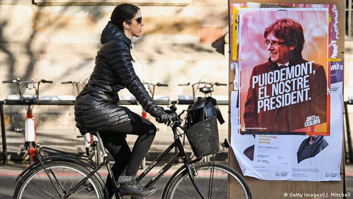 A woman biking past a poster showing Carles Puigdemont in Barcelona (Getty Images/J.J. Mitchell)
