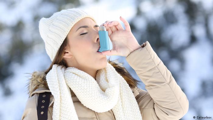A woman uses an inhaler