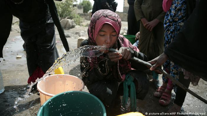 A child drinking water from a hose in Yemen