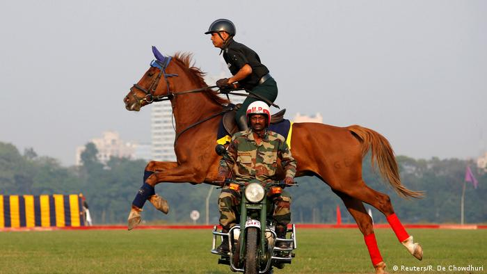 A horse and rider jumping over a moving motorcycle (Reuters/R. De Chowdhuri)
