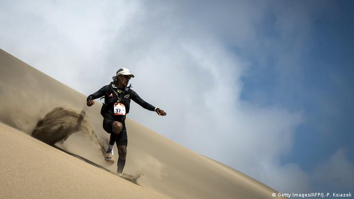A person running down a sand dune (Getty Images/AFP/J.-P. Ksiazek)
