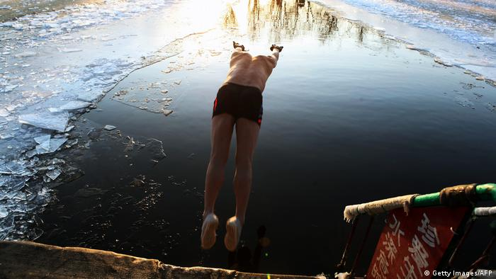 A person jumping into a lake partially covered in ice (Getty Images/AFP)