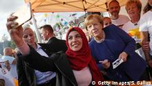 STRALSUND, GERMANY - SEPTEMBER 16: German Chancellor and Chrstian Democrat (CDU) Angela Merkel poses for a selfie with a young woman who came one year ago from Iran during a brief visit by Merkel to a local CDU-organized fest on September 16, 2017 in Stralsund, Germany. Merkel is seeking a fourth term in German federal elections scheduled for September 24 and currently has a double-digit lead over her main rival, German Social Democrat (SPD) Martin Schulz. (Photo by Sean Gallup/Getty Images)