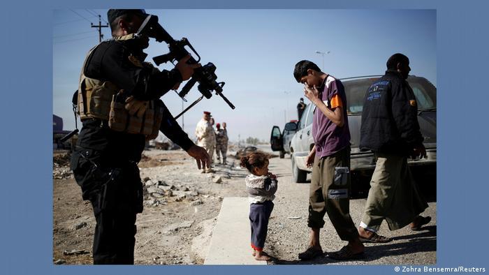 Garota que fugiu de Mossul, no Iraque, diante de soldado do Exército do país